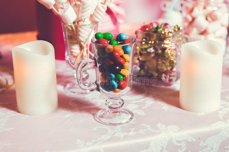 Colorful candy . Multi colored sweets . Colored candy in a glass . Round chocolate is very colorful . Candle stock photography