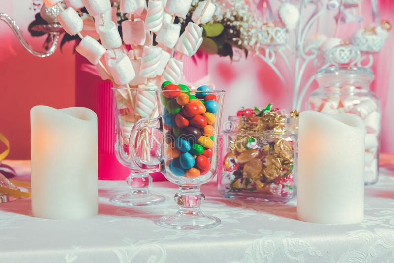Colorful candy . Multi colored sweets . Colored candy in a glass . Round chocolate is very colorful . Candle royalty free stock image
