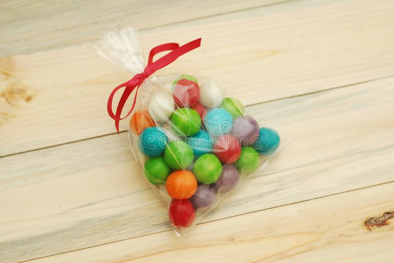 Colorful Candy are Stuffed in Transparent Plastic Bag with Bow Ribbon over Wooden background. Gifts for Birthday party. stock image
