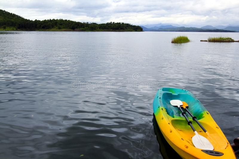 Colorful canoeing or kayak boat with two paddle floating on lake stock photo