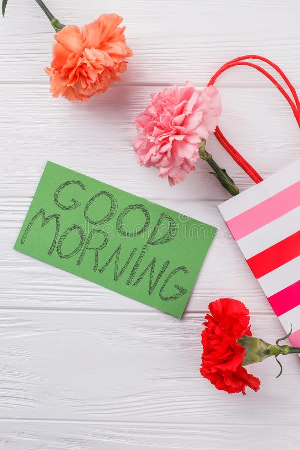 Colorful carnation flowers and good morning wish on note. Top view. White wooden background stock photo