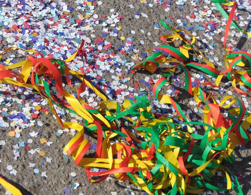 Colorful carnival background, garlands and confetti on asphalt. Colorful carnival background with garlands, streamer, confetti on asphalt stock images
