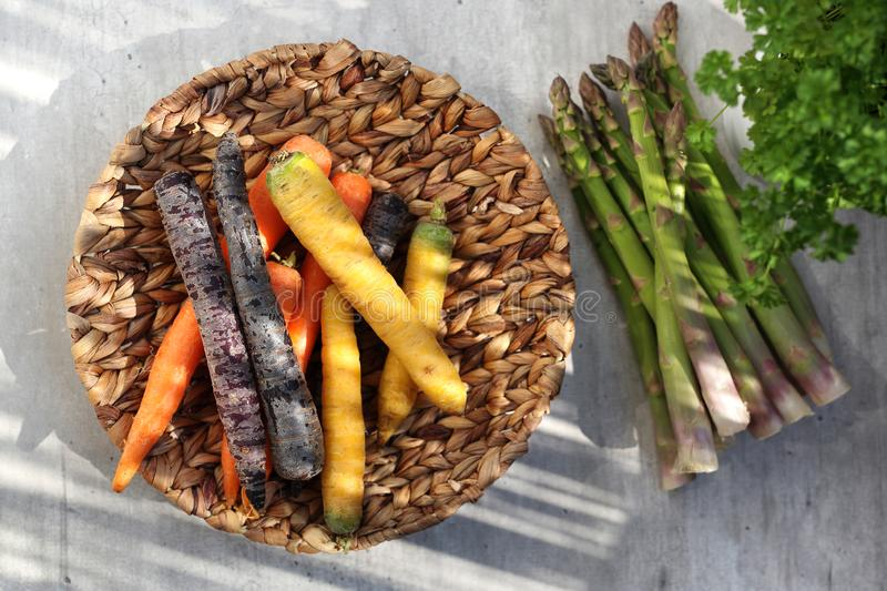 Colorful carrots and green asparagus. Basket with vegetables on a kitchen counter stock photos