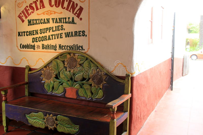 Colorful carved bench standing against wall of shop, Old Town, San Diego, California, 2016. Beautifully hand carved wood bench set in front of wall painted with royalty free stock images