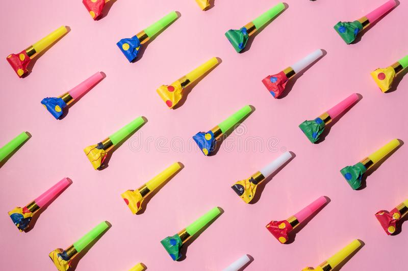 Colorful celebration pattern with party blower horns. Minimal party concept. Flat lay royalty free stock photos
