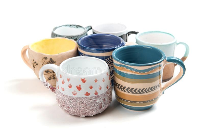 Colorful ceramic glazed cups on white background stock photography