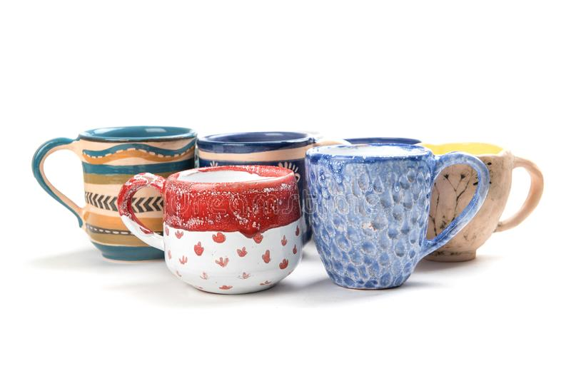 Colorful ceramic glazed cups on white background stock images