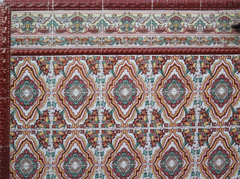 Colorful ceramic tiled corner of wall finish stock photography