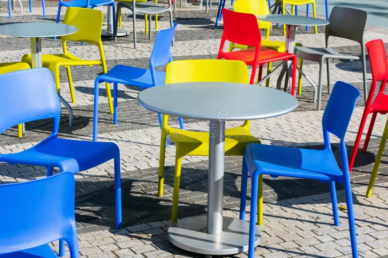 Colorful chair and grey round tables on uneven cobblestone pavement stock photos