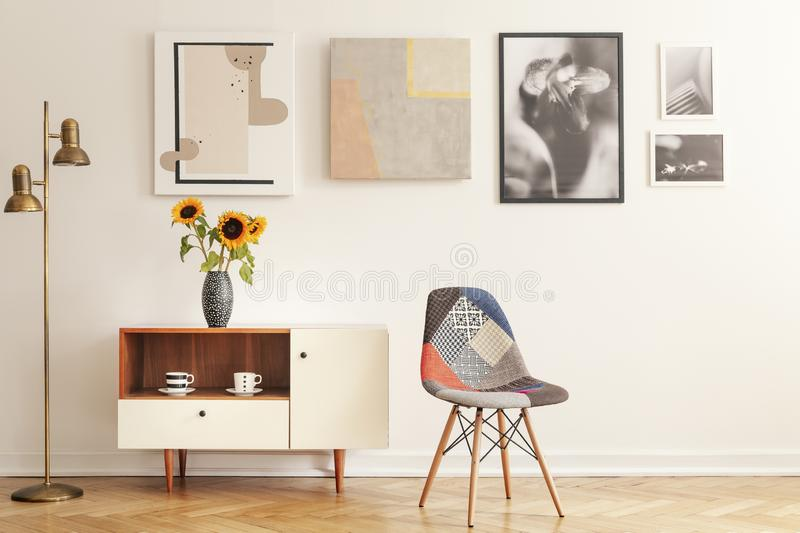 Colorful chair standing in white living room interior with gallery on wall, cupboard with flowers and tea cups stock images