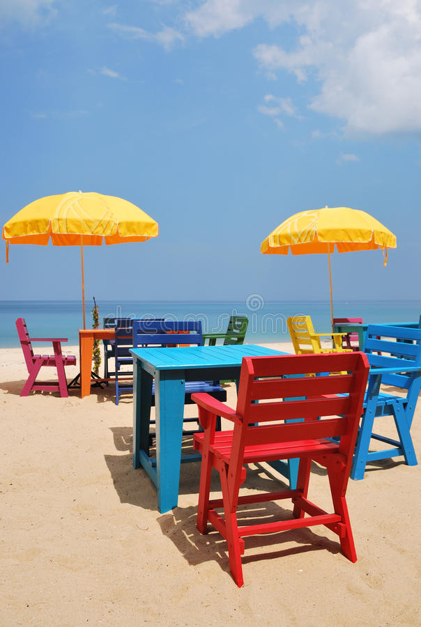 Colorful chair and table with yellow umbrella on the beach. With blue sky stock image