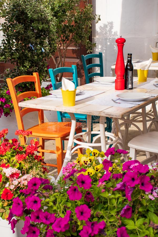 Colorful chairs and table in a restaurant with flowers royalty free stock image