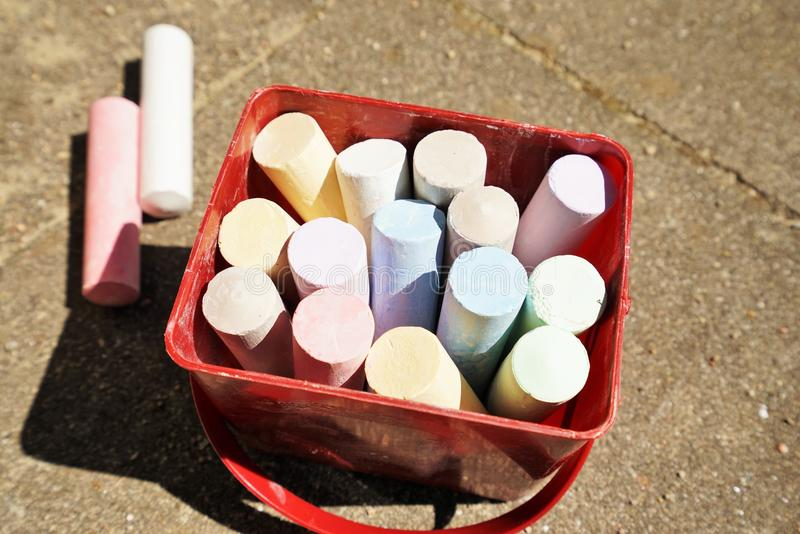 Colorful chalk in a box. Colorful chalk in a paintbox on a playground in summer royalty free stock images