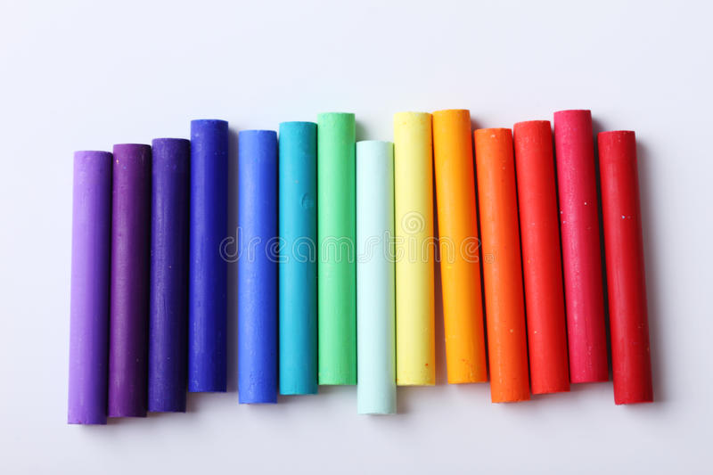 Colorful chalk pastels on white background. Arranged as rainbow spectrum stock image