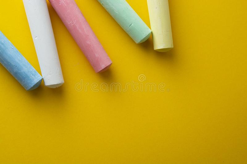 Colorful chalks over yellow background with copy space. Education template. Childhod, business and design stock image