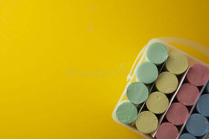 Colorful chalks over yellow background with copy space. Education template. Childhod, business and design royalty free stock photos