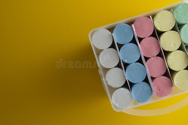 Colorful chalks over yellow background with copy space. Education template. Childhod, business and design royalty free stock photography