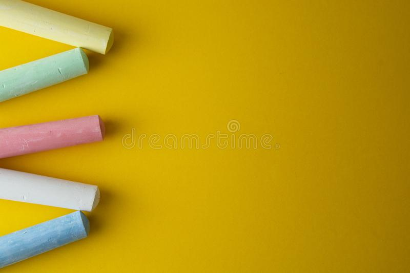 Colorful chalks over yellow background with copy space. Education template. Childhod, business and design royalty free stock images
