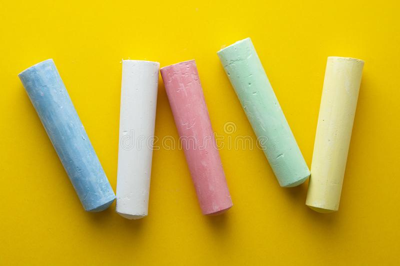 Colorful chalks over yellow background. Education template. Childhod, business and design royalty free stock photography