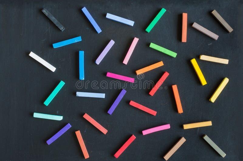 Colorful chalks seamless pattern on blackboard. Colorful chalks and soft pastels seamless pattern on blackboard background isolated stock image