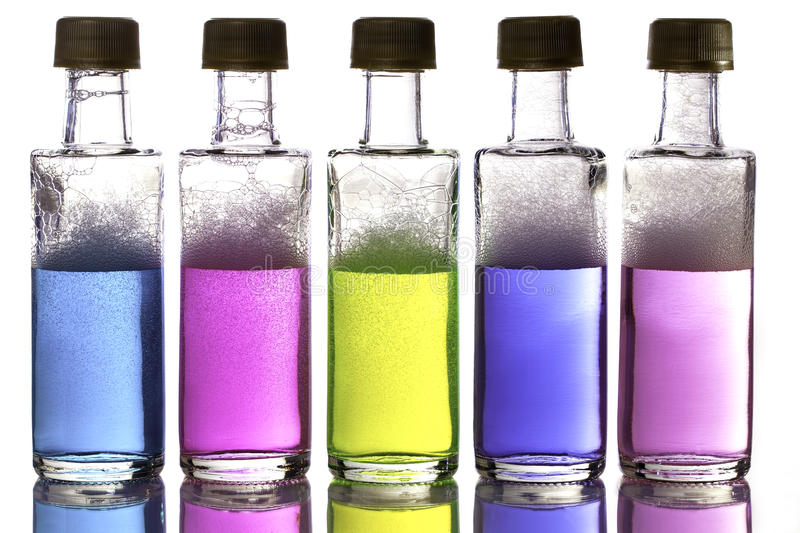 Colorful chemical ingredients in bottles. Colorful chemical ingredients in solution arranged in a row of bottles against a white background stock photos
