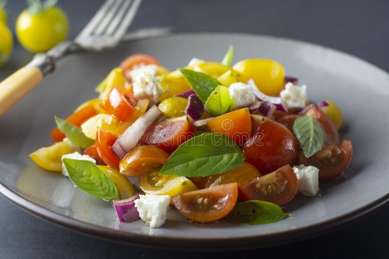 Colorful cherry tomatoes and basil salad on a plate, dark background. Healthy, summer food. Colorful cherry tomatoes and basil salad on a plate, dark background stock photos