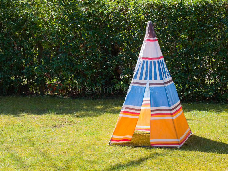 Colorful child's toy Teepee tent on the grass. Colorful child's toy Teepee tent of native american made of canvas on the grass in a sunny day stock photo