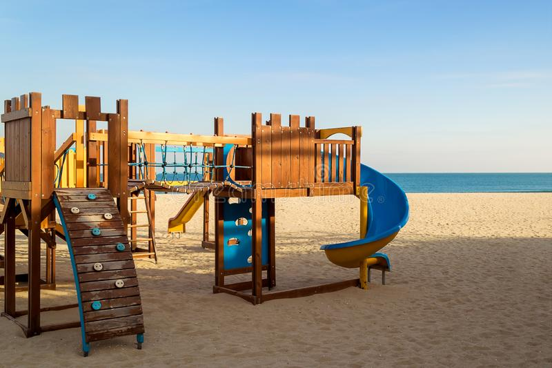 A colorful children playground on an empty sandy sea beach. Warm winter without snow, winter beach without people on a sunny day.  royalty free stock images