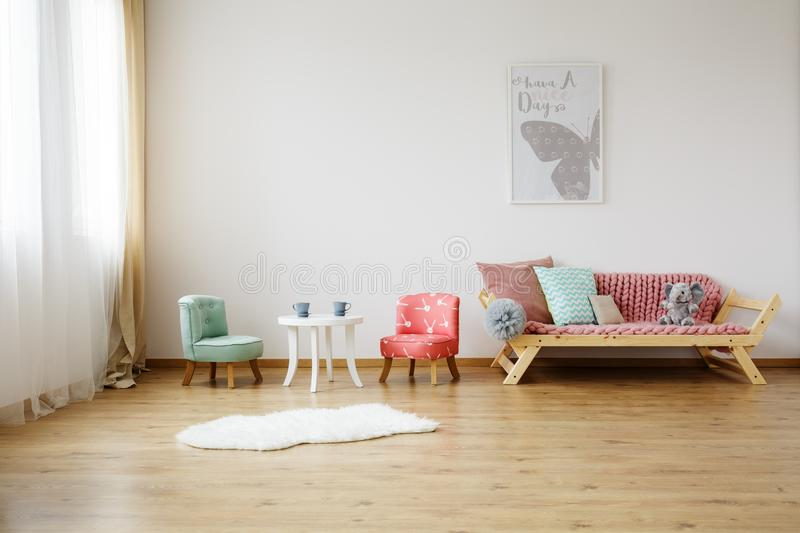 Colorful children`s chairs. And white table in bright room with mint pillow on sofa royalty free stock photography