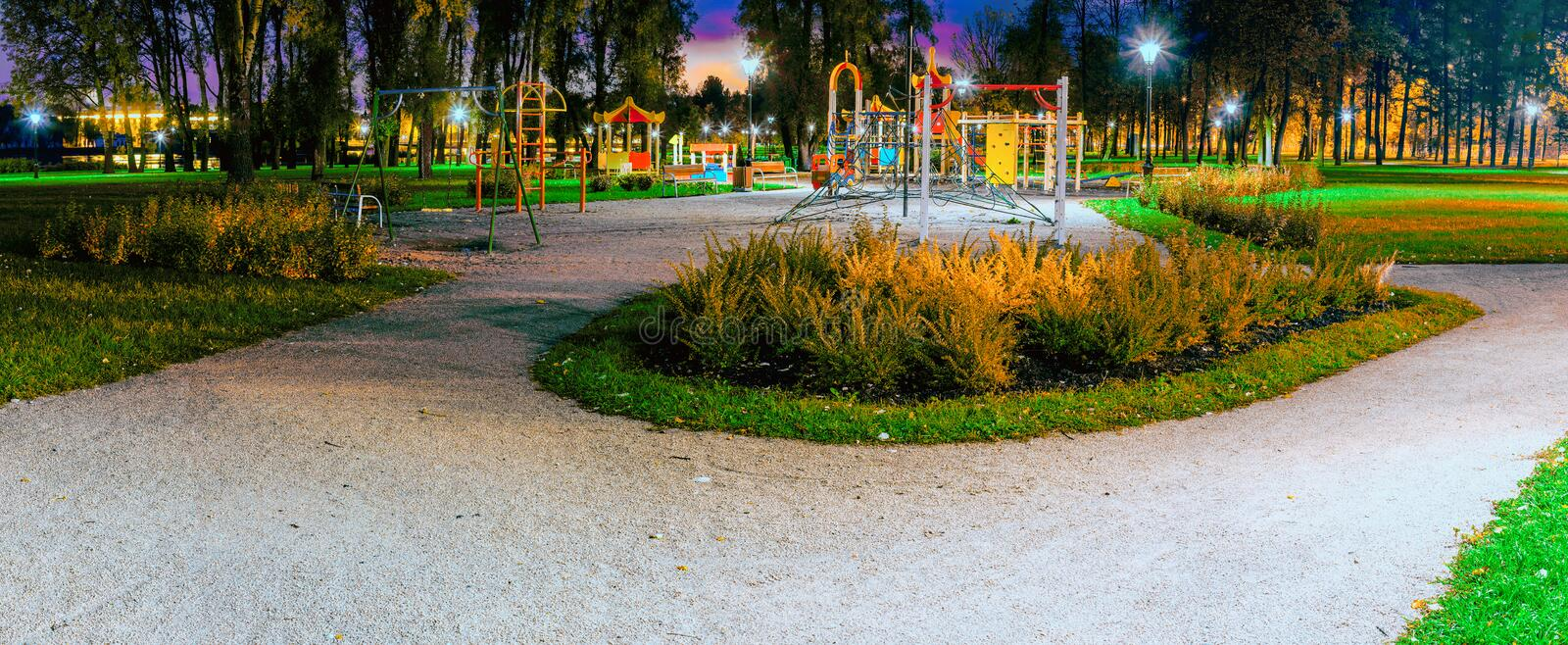 Colorful children`s Playground in the light of the night lanterns. Night city landscape. Colorful playground in the light of night lights. Night city landscape stock image