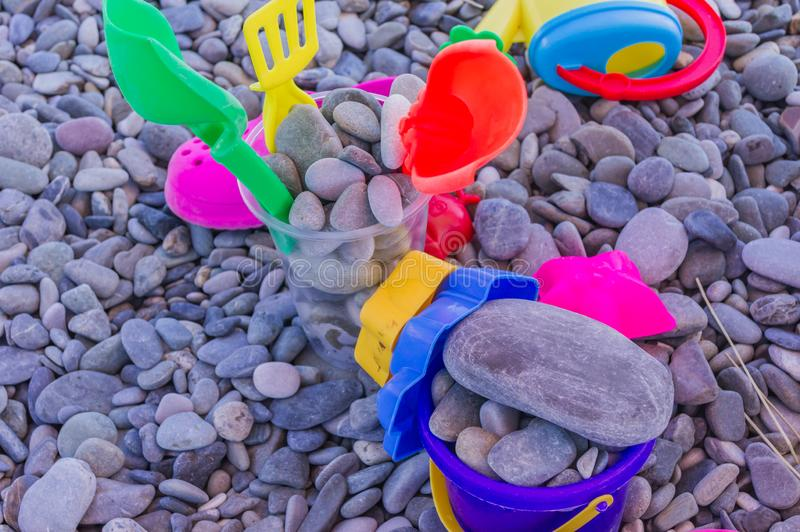 Colorful children toys on pebble beach. Leisure and vacation concept.  stock photo