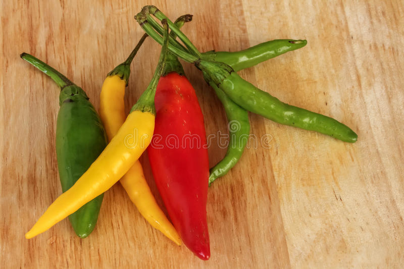 Colorful chili - red, green, yellow - wood background royalty free stock images