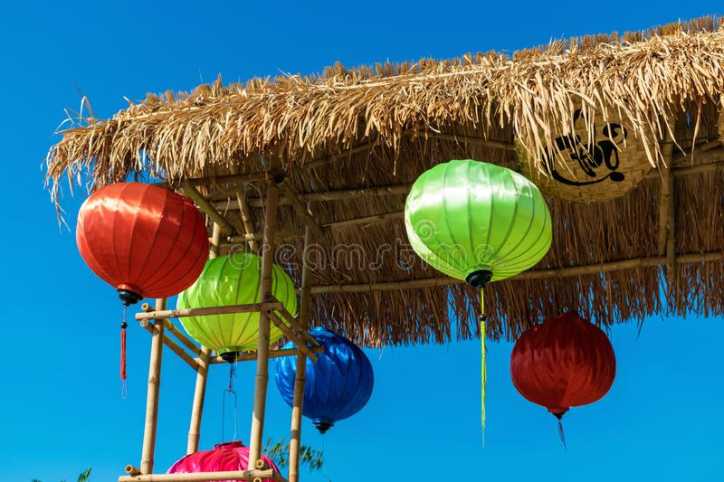 Colorful Chinese lanterns under the thatch roof under sunlight. Colorful Chinese lanterns under thatch roof under sunlight, culture, traditional, asian, china royalty free stock photo
