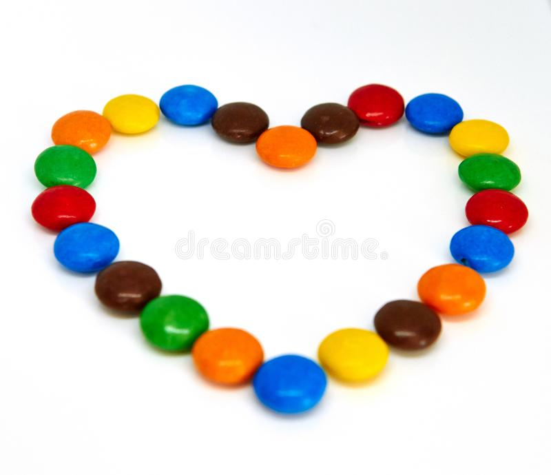 Colorful chocolate buttons. In the shape of heart on a white background abc abstract alphabet blue bright brown candy celebration children concept creative stock photos