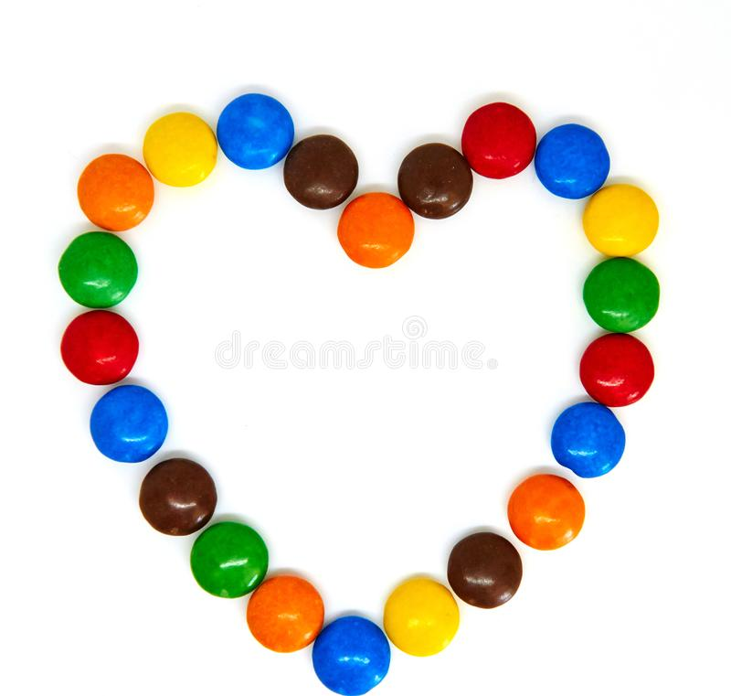 Colorful chocolate buttons. In the shape of heart on a white background abc abstract alphabet blue bright brown candy celebration children concept creative royalty free stock photo