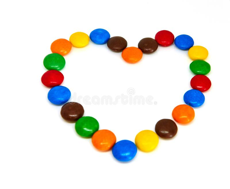 Colorful chocolate buttons. In the shape of heart on a white background abc abstract alphabet blue bright brown candy celebration children concept creative stock photo