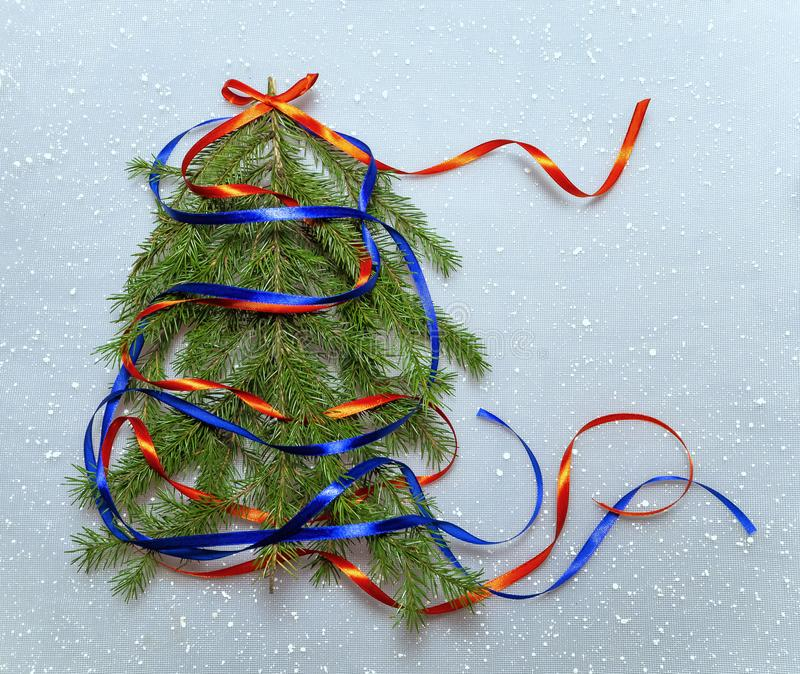 Colorful christmas background with christmas tree. Red and blue ribbons adorn the spruce. On top of a tree is a red bow stock photos