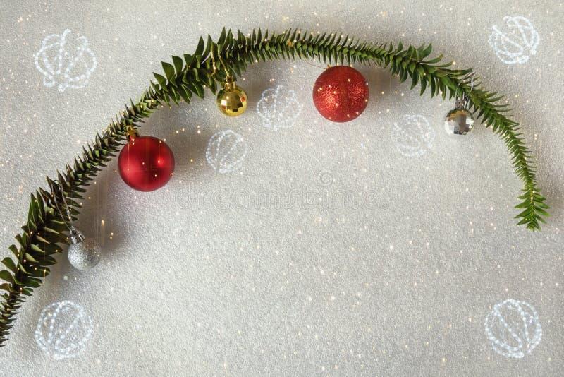 Colorful Christmas balls on branch of bunya pine; bright festoon illumination - digital composite royalty free stock photo