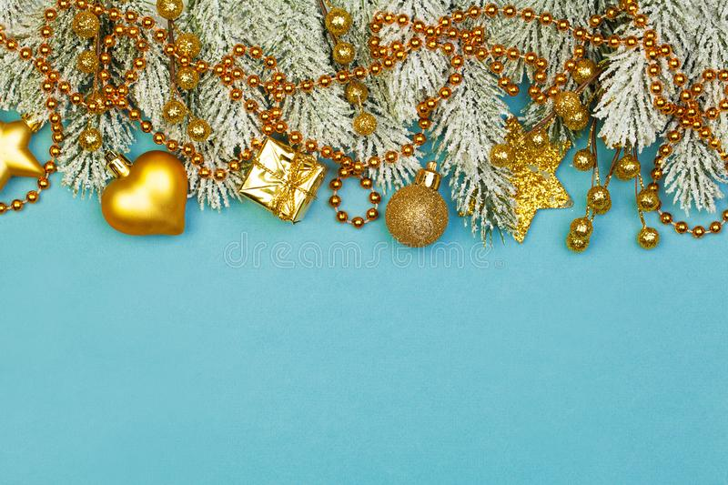 Colorful Christmas border background. Xmas holiday composition with gold garland, berries, gifts and green fir branch on blue. Background royalty free stock photos