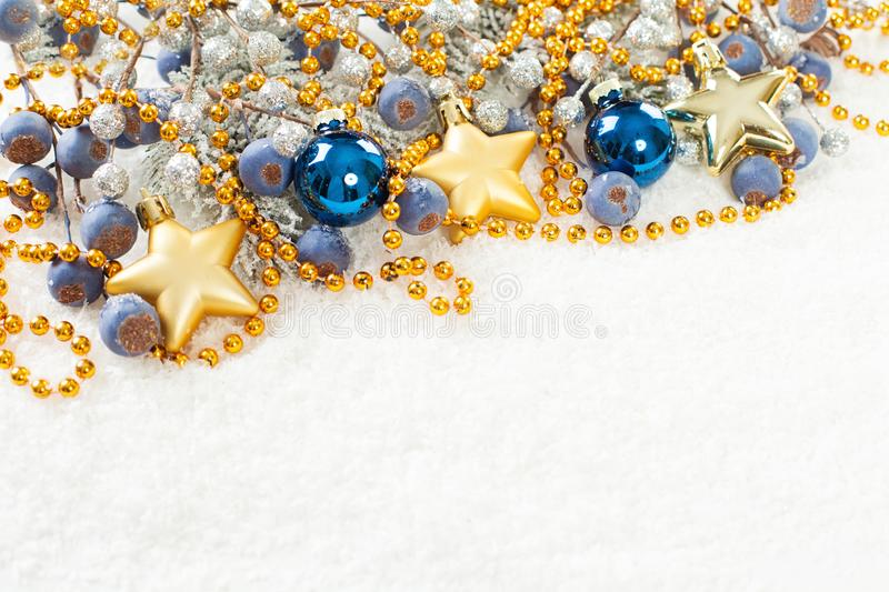 Colorful Christmas composition with green Xmas fir branch, gold garland, blue glass baubles and berries on white snow background.  royalty free stock images