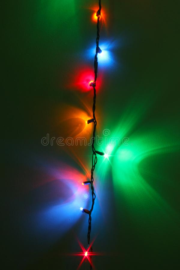 Colorful Christmas Holiday Lights Reflecting on Wall. Pretty Christmas Holiday lights reflecting against green wall. Colorful string of star lights with copy stock photography