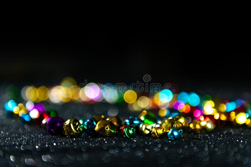 Colorful Christmas jingle bells. Black blurred background. Copy space. stock photo