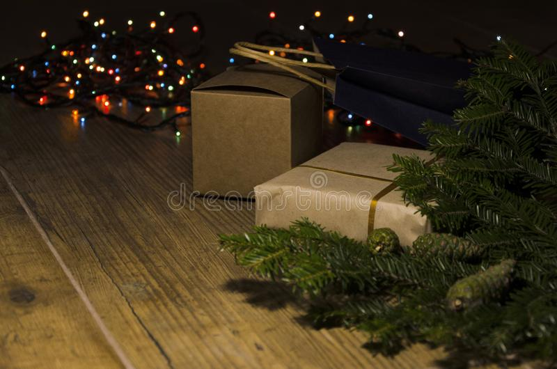 Colorful Christmas lights, fir tree and cones, gifts on the wooden rustic floor. Concept of coxzy Christmas Eve royalty free stock photography