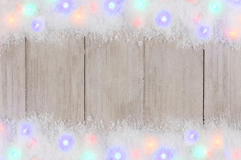 Colorful Christmas lights in snow double border over white wood. Colorful Christmas lights in snow double border, above view on a light gray wood background royalty free stock photos