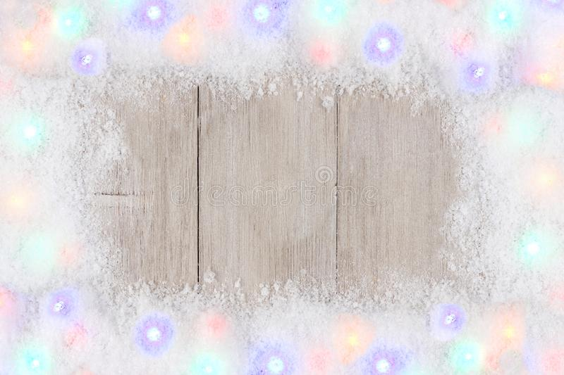 Colorful Christmas lights in snow frame over white wood. Colorful Christmas lights in snow frame, above view on a light gray wood background stock photography