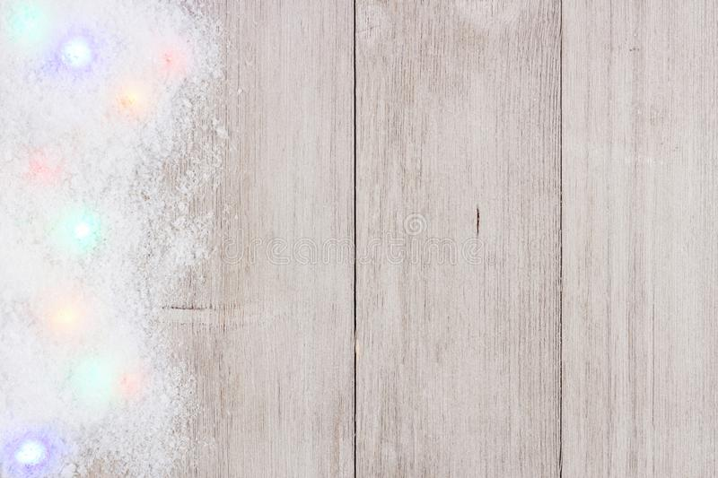 Colorful Christmas lights in snow side border over white wood. Colorful Christmas lights in snow side border, above view on a light gray wood background stock photos