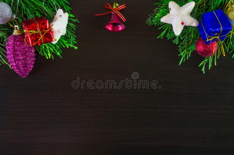 Colorful Christmas ornaments and pine tree branches on corner of wooden background. Brown blank aerial royalty free stock photos