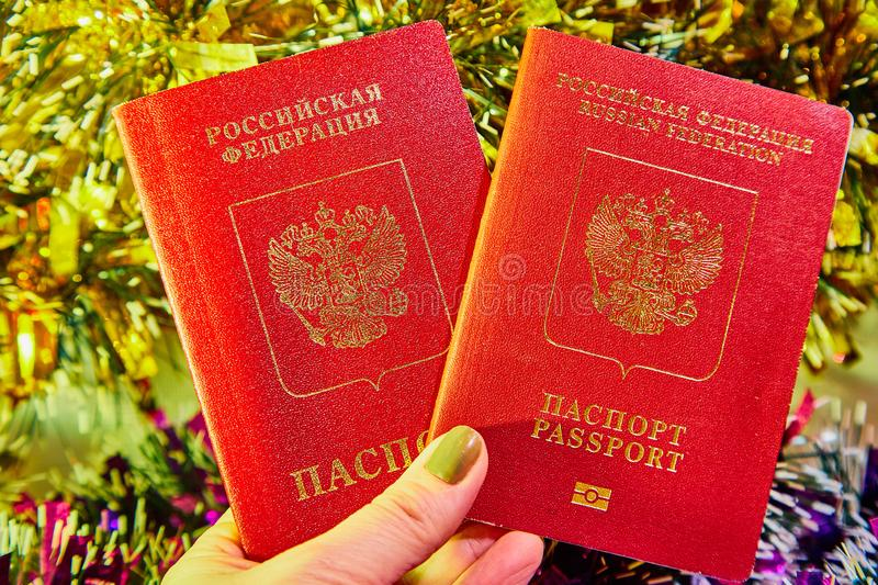 Colorful Christmas tinsel and passport citizen of Russia in woman hand stock photography