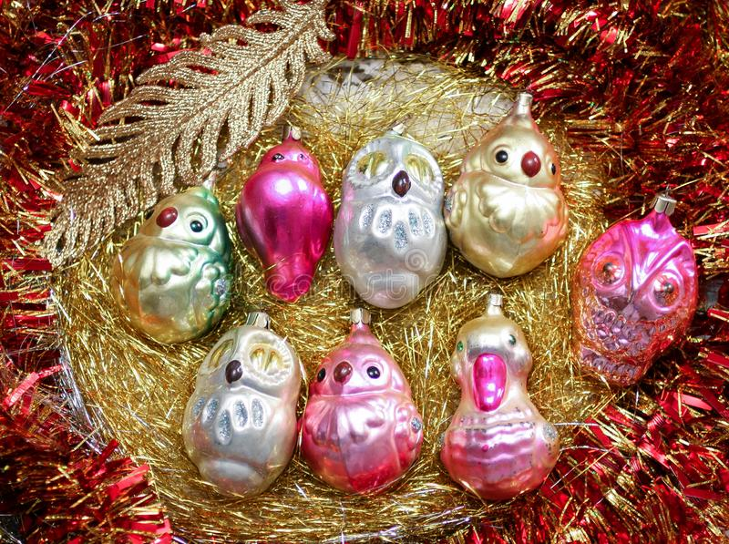Colorful Christmas toys different birds and a golden feather on a golden tinsel royalty free stock photos