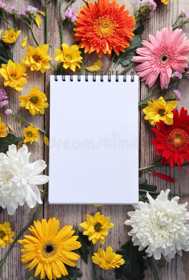 Colorful chrysanthemums placed on the table old wooden with book diary stock image